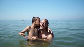 Padre e hijo que juegan en la forma de vida feliz de la diversión del retrato de la playa junto fotografía de archivo