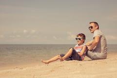 Padre e hijo que juegan en la playa en el tiempo del día Foto de archivo libre de regalías