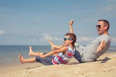 Padre e hijo que juegan en la playa en el tiempo del día Fotos de archivo libres de regalías