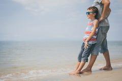 Padre e hijo que juegan en la playa en el tiempo del día Fotografía de archivo libre de regalías