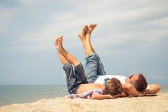 Padre e hijo que juegan en la playa en el tiempo del día Fotos de archivo