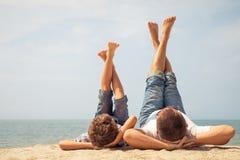 Padre e hijo que juegan en la playa en el tiempo del día Imagenes de archivo