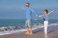 Padre e hijo que juegan en la playa en el tiempo del día Concepto de Fotos de archivo libres de regalías