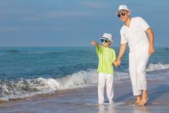 Padre e hijo que juegan en la playa en el tiempo del día Concepto de Foto de archivo