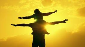 Padre e hijo que juegan en la silueta del cielo de la tarde almacen de metraje de vídeo