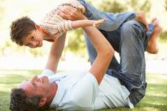 Padre e hijo que juegan junto en parque
