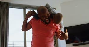 Padre e hijo que juegan junto en un hogar cómodo 4k almacen de metraje de vídeo