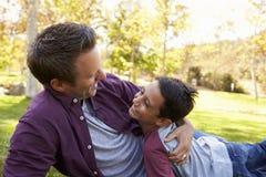 Padre e hijo que mienten abajo abrazando en un parque Imagen de archivo libre de regalías