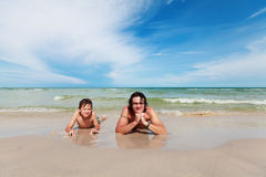 Padre e hijo que mienten en la playa arenosa. Imagenes de archivo