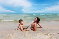 Padre e hijo que mienten en la playa arenosa. Fotos de archivo