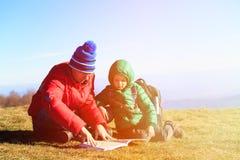 Padre e hijo que miran el mapa en montañas escénicas Fotografía de archivo