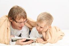 Padre e hijo que miran la almohadilla táctil en dormitorio Foto de archivo