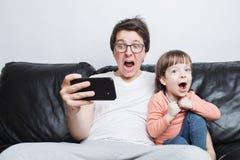 Padre e hijo que miran un vídeo asustadizo en el teléfono que se sienta en un sofá en un fondo blanco Están gritando Un niño pequ imágenes de archivo libres de regalías