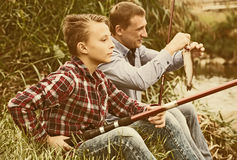 Padre e hijo que pescan junto en el lago Fotografía de archivo