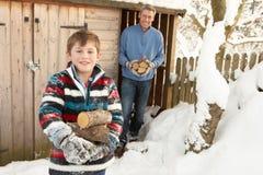 Padre e hijo que recogen registros de almacén de madera Imagen de archivo