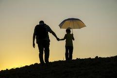 Padre e hijo que recorren en la puesta del sol Foto de archivo libre de regalías