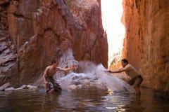Padre e hijo que salpican alrededor en el agua imagen de archivo