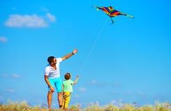 Padre e hijo que se divierten, jugando con la cometa junto Foto de archivo libre de regalías