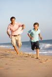 Padre e hijo que se ejecutan a lo largo de la playa del verano Imagen de archivo libre de regalías