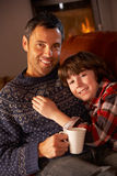 Padre e hijo que se relajan con la bebida caliente que ve la TV Imagen de archivo libre de regalías
