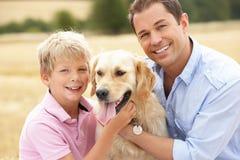 Padre e hijo que se sientan con el perro en las balas de la paja adentro Imágenes de archivo libres de regalías