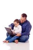 Padre e hijo con un ordenador portátil Foto de archivo