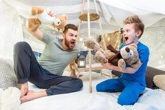 Padre e hijo que se sientan en el fuerte combinado y que juegan con los osos de peluche Fotografía de archivo libre de regalías
