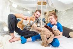 Padre e hijo que se sientan en el fuerte combinado y que juegan con los osos de peluche Fotos de archivo libres de regalías