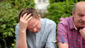Padre e hijo que sientan ser al aire libre triste y dissapointed con noticias metrajes