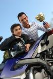 Padre e hijo que sostienen el trofeo foto de archivo libre de regalías