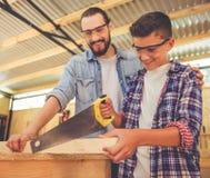 Padre e hijo que trabajan con madera Foto de archivo libre de regalías