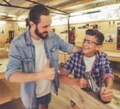 Padre e hijo que trabajan con madera Imagen de archivo