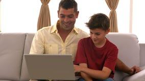 Padre e hijo que usa el ordenador portátil en el sofá almacen de video