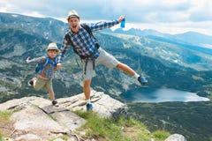 Padre e hijo que viajan en las montañas Bulgaria de Rila fotografía de archivo
