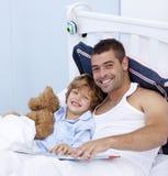Padre e hijo sonrientes que leen un libro en cama Imagen de archivo libre de regalías