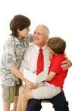 Padre e hijos con la tarjeta de felicitación Fotos de archivo