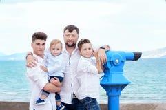 Padre e hijos en el mar Familia en la plataforma de la visión cerca de la moneda imágenes de archivo libres de regalías