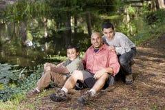 Padre e hijos hispánicos del retrato al aire libre por la charca Fotos de archivo