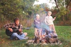 Padre e hijos que asan las melcochas y que tocan la guitarra por el campo fotos de archivo libres de regalías