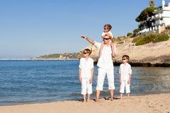 Padre e hijos que caminan en la playa Imágenes de archivo libres de regalías