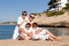 Padre e hijos que caminan en la playa Fotos de archivo libres de regalías