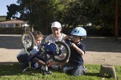Padre e hijos que fijan la bici Imágenes de archivo libres de regalías