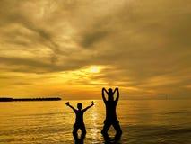 Padre e hijos que hacen frente a puesta del sol Foto de archivo libre de regalías