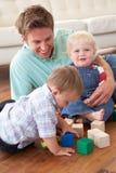 Padre e hijos que juegan con los bloques coloreados en Ho fotos de archivo libres de regalías