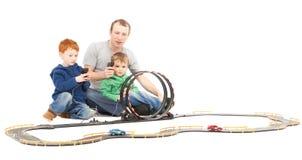 Padre e hijos que juegan a los cabritos que compiten con el juego del coche del juguete imagen de archivo libre de regalías