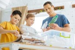 Padre e hijos que preparan las botellas plásticas para reciclar Foto de archivo libre de regalías