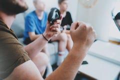 Padre e hijos que se sientan en un sofá en sala de estar y que juegan a los videojuegos Concepto relajante del tiempo de la famil Fotografía de archivo