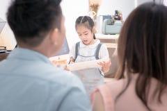 Padre e madre asiatico che guarda la pittura del bambino della figlia Fotografia Stock Libera da Diritti