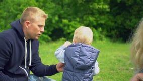 Padre e madre che gioca con il figlio in parco stock footage