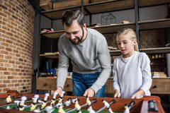 padre e piccola figlia che giocano insieme calcio-balilla fotografia stock